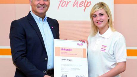 Leonie Zeiger wird eine Urkunde von medi for help ueberreicht