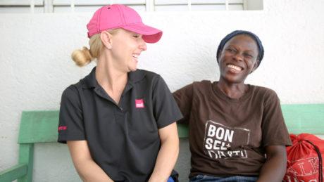 Lachende medi for help Freiwillige mit einer fröhlichen Haitianerin auf einer Bank