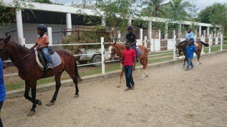 Drei haitianische Kinder reiten auf Pferden, die von Erwachsenen geführt werden