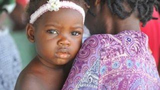Haitianerin mit ihrem Baby auf dem Arm