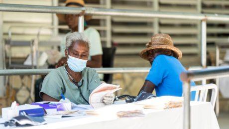 Haitianer wartet auf Behandlung während Frau Dokumente ausfüllt
