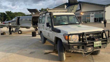 Auto und Flugzeug auf Rollfeld in Haiti