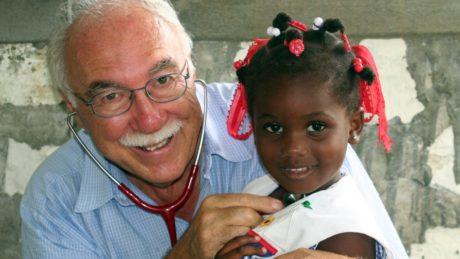 Dr. Rolf Maibach hält ein Mädchen auf dem Arm und hört es mit dem Stethoskop ab